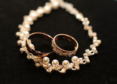 Gold wedding rings and necklace on black background — 图库照片