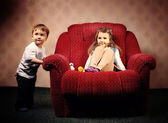 Move to another apartment, the children move a large red chair — Stock Photo