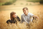 Young man and woman sitting in a field of wheat — Foto de Stock