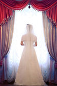 Bride standing at the window — Stock Photo