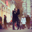 Lovers kissing and cuddling on a city street with passers — Stock Photo