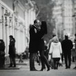 Lovers kissing and cuddling on a city street with passers — Stock Photo #22170809