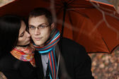 Young couple under an umbrella in the autumn forest — Stock Photo