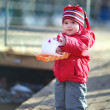 Little cheerful girl 2-3 years, runs the boats in the spring puddle — Stock Photo