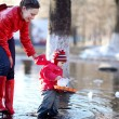 Stock Photo: Little cheerful girl 2-3 years, runs boats in spring puddle with her mother
