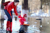 Little cheerful girl 2-3 years, runs the boats in the spring puddle with her mother — Stock Photo