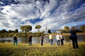 Tourists looking at the church on a river — Stock Photo