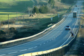 Highway road with cars through the field — Stock Photo