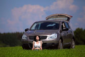 Beautiful woman sit in front of car in a field — Stock Photo