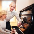 Beautiful young man and woman sitting and playing the piano at the wedding — Stock Photo #35646871