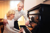 Beautiful young man and woman sitting and playing the piano at the wedding — Stock Photo