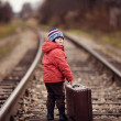 Stock Photo: Little traveler with a suitcase on the railroad