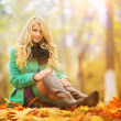Girl in the autumn park with yellow leaves — Stock Photo