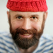 Portrait of a funny man with beard and read hat — Stock Photo