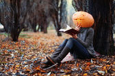 Halloween girl with pumpkin head — Stockfoto