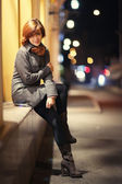 Cheerful smiling girl in an autumn night city — Stock Photo