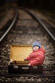 Boy sitting in a suitcase near the railway journey — Stock Photo