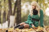 грустная девушка, сидя на желтые листья — Стоковое фото