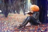Halloween girl with pumpkin head — Stock Photo