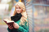 Girl reading a book in autumn park — Foto Stock