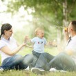 Happy young mother playing with baby in the park — Stockfoto