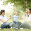 Happy young mother playing with baby in the park — Stock Photo #36344391