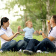 Happy young mother playing with baby in the park — Stock Photo #36344437