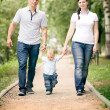 Happy young family mom dad and baby in the park — Stok fotoğraf