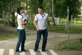 Happy young family mom dad and baby in the park — Stock Photo