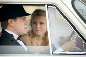 Groom and bride in car — Stock Photo