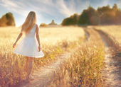 Girl running in wheat field — Stock Photo