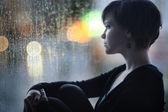 Sad girl on the windowsill looking out the window — Stock Photo