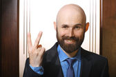 Bearded man showing victory gesture — Stock Photo