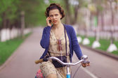 Woman with phone on bicycle — Stock Photo