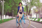 Woman with phone on bicycle — Stock fotografie