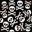 Skulls and bones on messy confetti Halloween seamless pattern on dark background — Stock Vector
