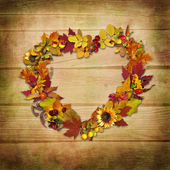 Wreath of autumn leaves on a wooden background — Stock Photo