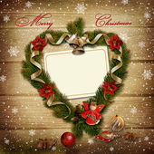 Card with wreath of pine branches on snowy wooden background — Stock Photo
