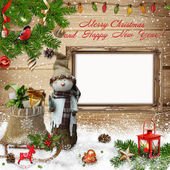 Christmas decoration with snowman, gift bag and the frame on a wooden background — Stock Photo