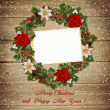 Christmas wreath with frame on wooden background — Stock Photo