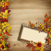 Frame with autumn leaves and berries on a wooden background — Stock Photo