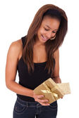 Beautiful young woman holding a gift, isolated on white — Stock Photo