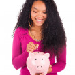 Young african american woman putting coin in piggy bank — Stock Photo #33297857