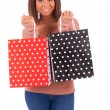 Beautiful african woman holding a credit card and shopping bags — Stock Photo #45689683