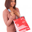 Beautiful african woman holding a credit card and shopping bags — Stock Photo #45689691