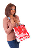 Beautiful african woman holding a credit card and shopping bags — Stock Photo