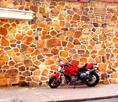 Shiny Red Motorcycle Parked By Stone Wall — Stock Photo