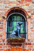 Small window with a dog statue — Stock Photo