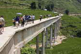 Unidentified tourists and locals cross concrete bridge — Stock Photo