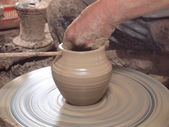 Potter makes on the pottery wheel clay pot. The hands of a potter with the tool, close-up. — Stock Photo